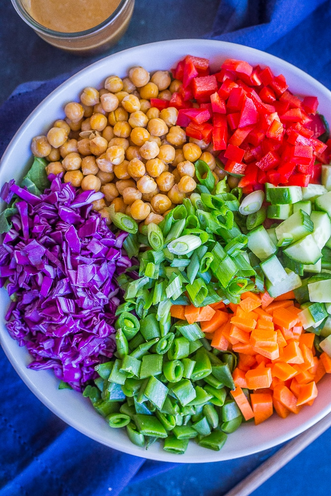 Asian Chickpea Chopped Salad in a big bowl with a napkin and jar of dressing
