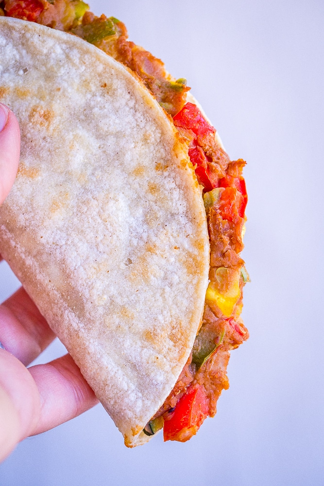 A crispy baked taco with summer vegetables being held in a hand so you can see the filling