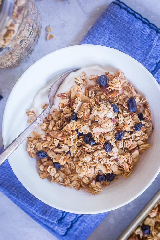 A bowl of Homemade Blueberry Almond Granola with yogurt on a blue napkin