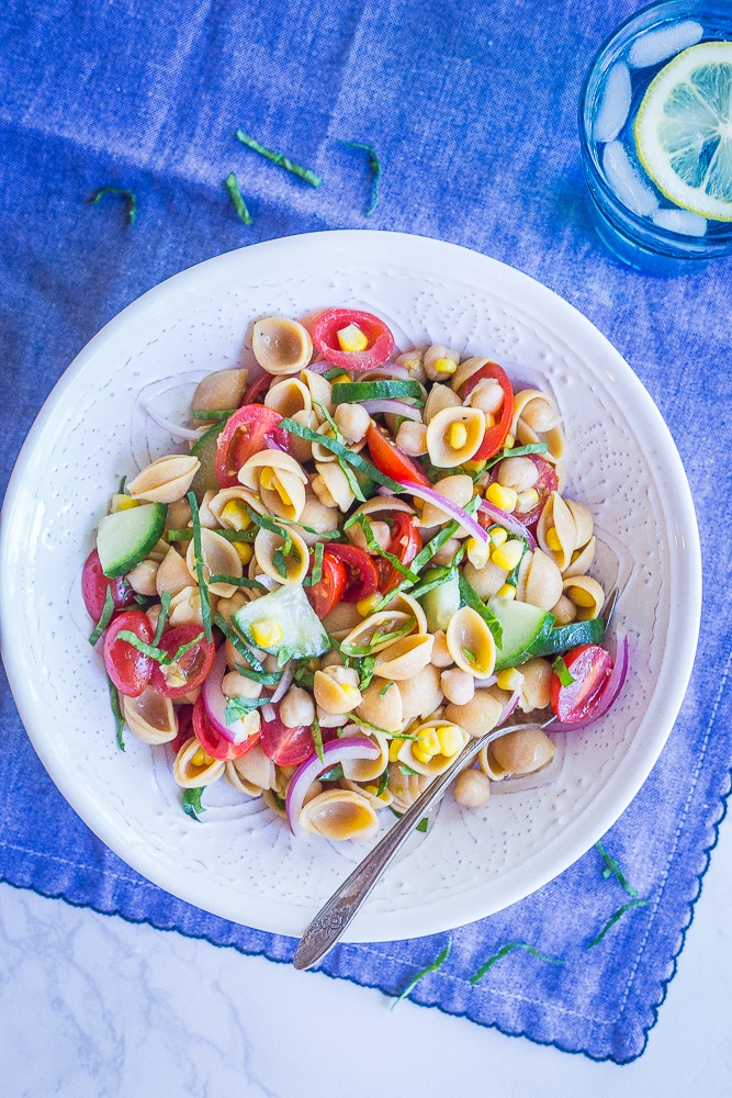 Bowl of summer vegetable pasta salad on a blue tablecloth