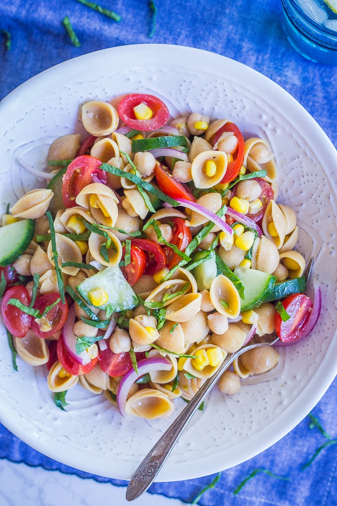 Bowl of summer vegetable salad with chickpeas on a blue tablecloth