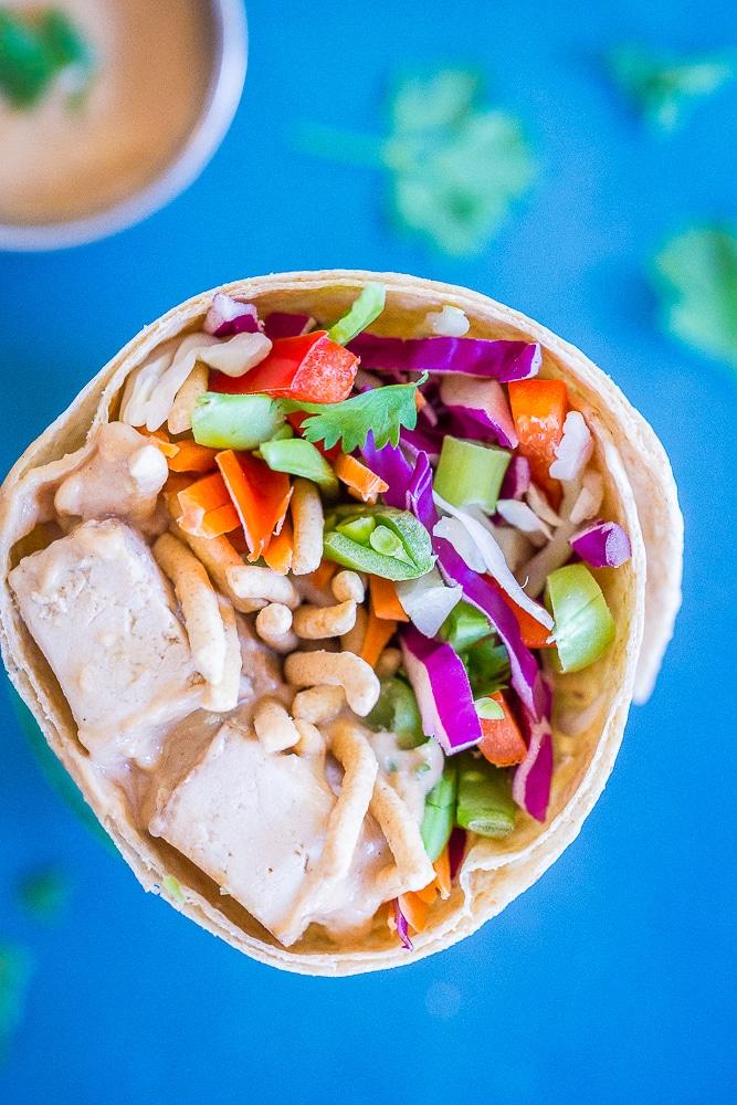 Close up of a Crunchy Asian Tofu Peanut wraps against a blue background