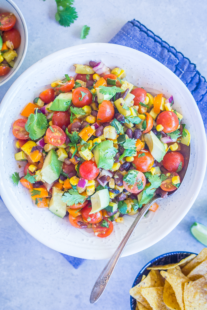 A big bowl of Loaded Summer Vegetable Salad with Black Beans on a blue napkin with a side of chips.