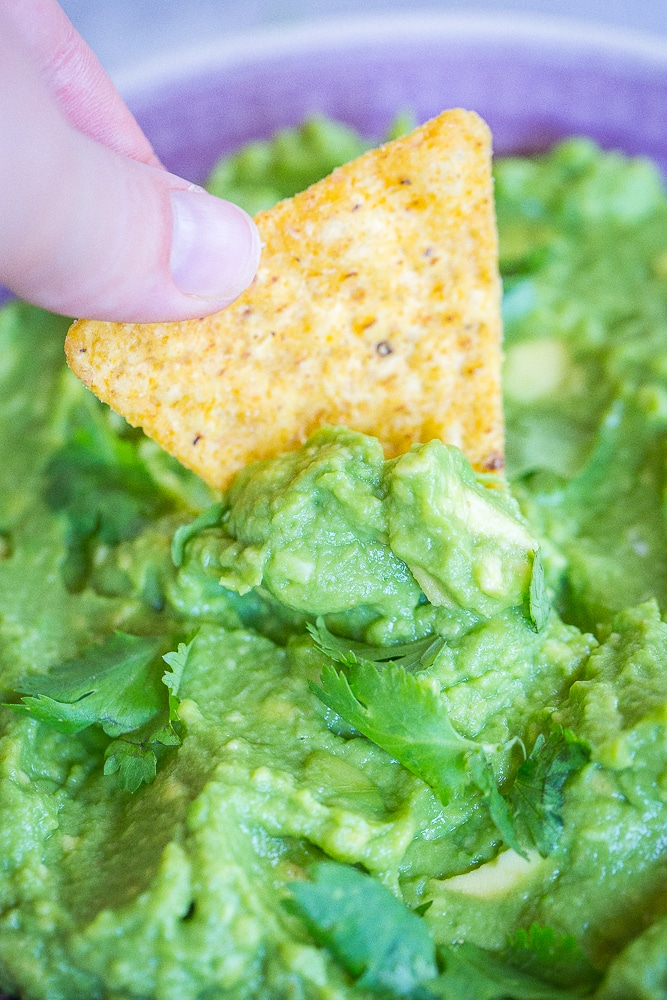 A chip dipping into The Best Easy Guacamole Recipe