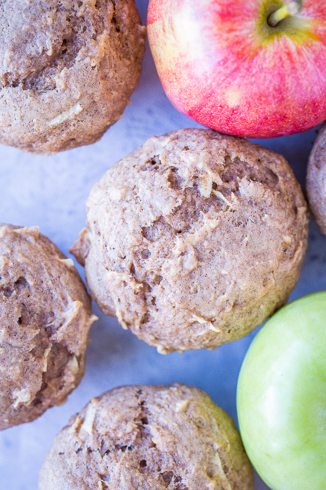 Close up of Best Healthy Apple Cinnamon Muffins on a table with apples