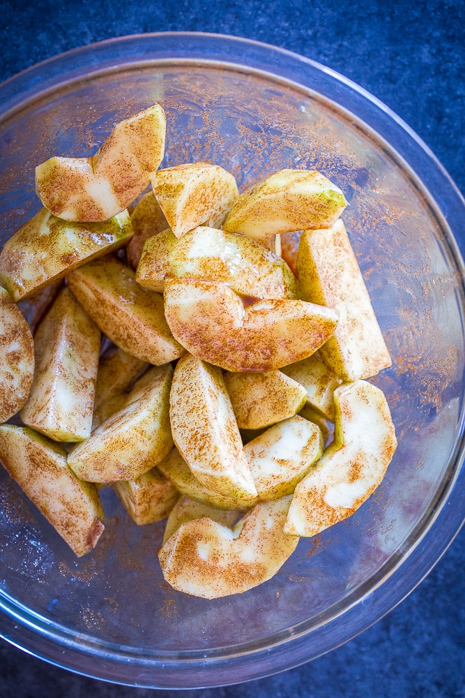 Apple slices in a bowl with cinnamon and sugar for Easy Apple Pie Bites