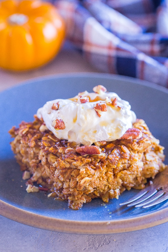 Slice of Make Ahead Pumpkin Pie Baked Oatmeal on a plate with whipped cream on top