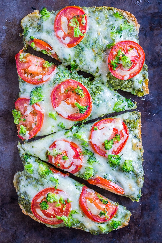 30 Minute Vegetarian French Bread Pizzas with Pesto, Tomato and Broccoli cut into slices on a sheet pan