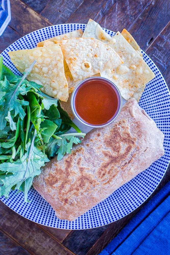 Make Ahead Bean Burritos on a plate with salad and chips