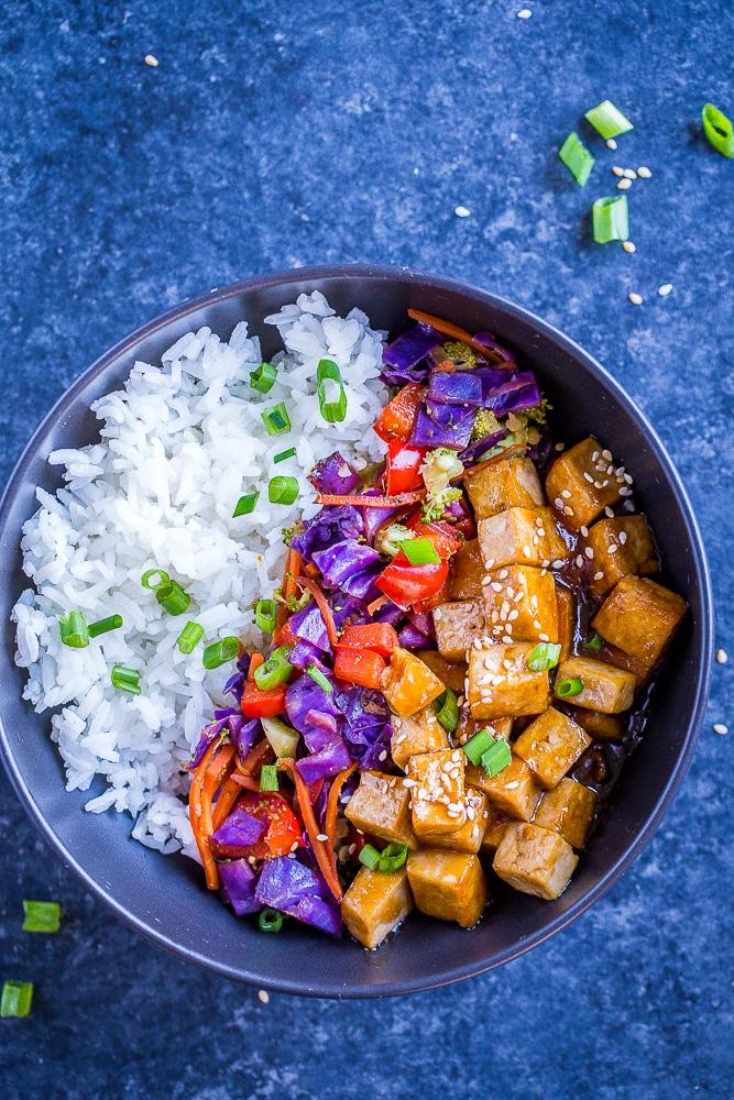 Sesame Ginger Tofu Meal Prep Bowls on a black background