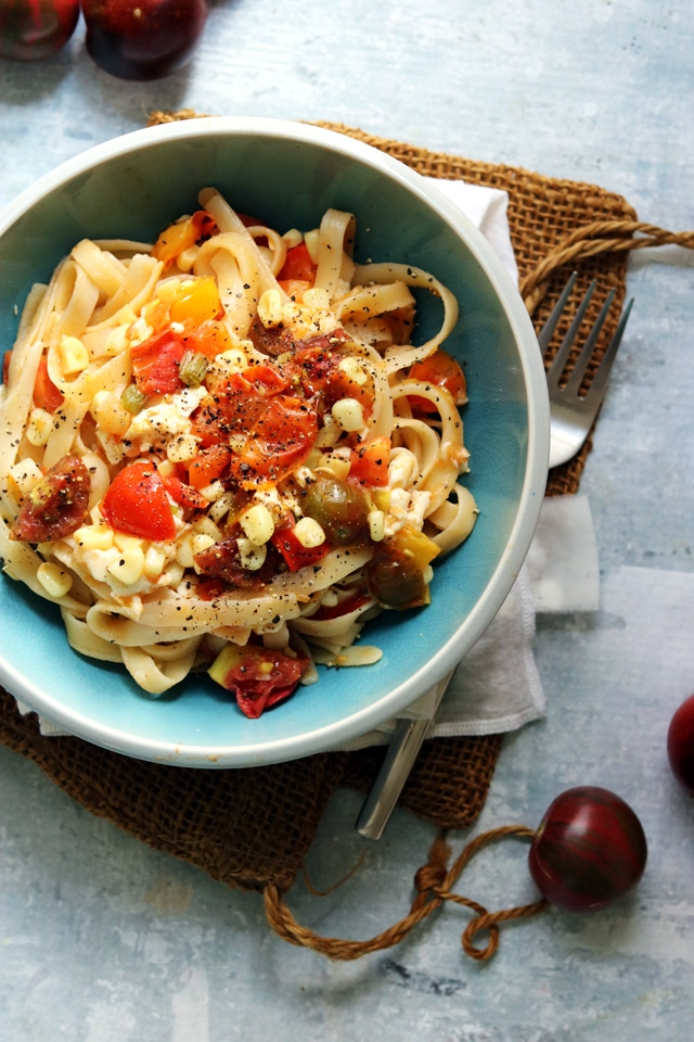 Summer corn and tomato pasta in a blue bowl