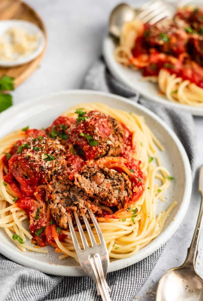 Vegan meatballs and sauce over spaghetti with a fork