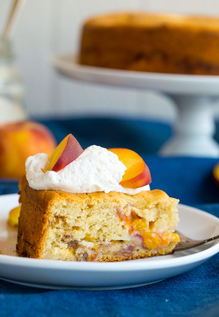 Slice of peach cake with whipped cream and fresh peaches on top