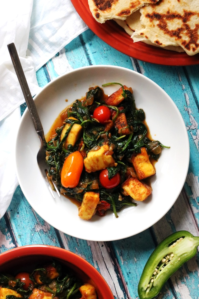palak paneer with tomatoes in a white bowl